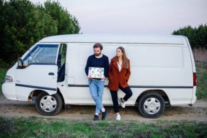 Young couple leaning on a white van | Can You Rent A Van If You Are Under 25?