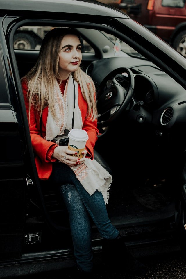 woman-sitting-in-car-while-holding-coffee-cup-3789854 (1)